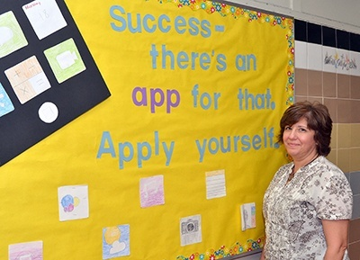 St. Helen School principal Annette Buscemi pauses by a poster in the school's hallway.