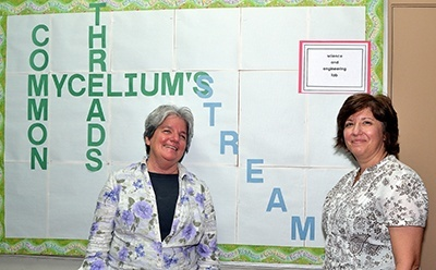 Carrie Roach, left, and Annette Buscemi show a poster at St. Helen School. Roach designed the poster after learning that threads of the Mycelium fungus can interlink to form a circle.