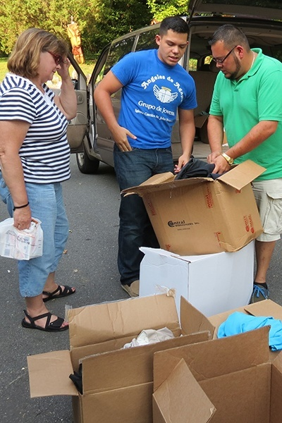 Miami seminarians Andres Pareja (right) and Nick Toledo select donated items to take on one of their daily visits with migrants. Local parishioner Mary Branisteanu, who coordinated collection, is at left.