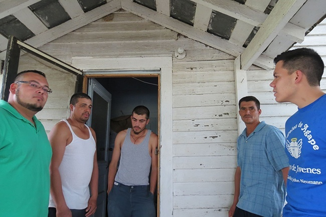 Miami seminarians Andres Pareja (left) and Nick Toledo (far right) spend time listening to Mexican migrant workers on the porch of the old farmhouse where they live.