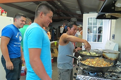 Miami seminarian Nick Toledo (left) watches migrant workers who have the evening's cooking duty for their camp.
