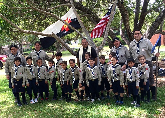 Father Jesus Arias, pastor of Good Shepherd, poses with leaders and members of the Stella Maris Otters as the boys proudly display the patches they received after making their promise as Otters.