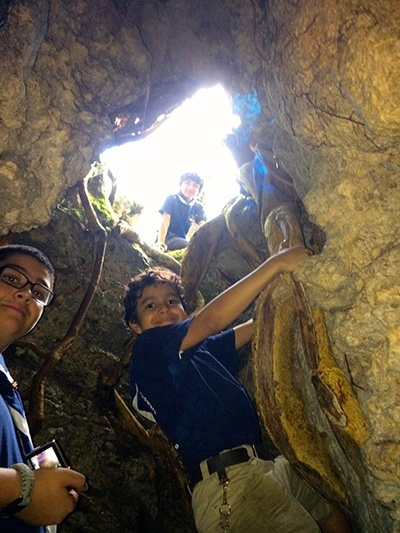 Explorer Leo Gonzalez, and Timber Wolves Christian Marmolejos and Luis Gonzalez explore a cave during the Stella Maris Explorers campout at Camp Owaissa Bauer in February 2014.