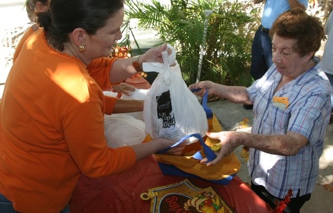 Esther Cabrera receives a donated turkey from a volunteer.