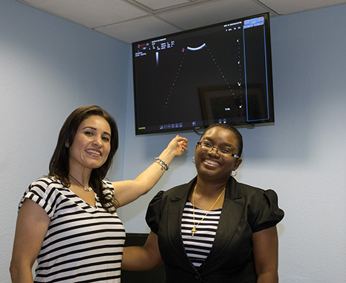 Ultrasound Technician Lorena Villaneda Romero Left Points To A Big Screen Television